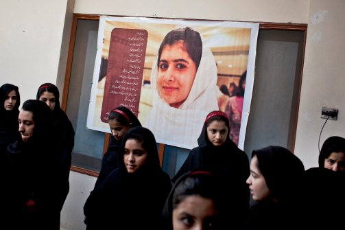 Pakistani school children gather under a giant poster of Malala at the Khushal School for Girls patio where they are waiting to be collected before classes in Mingora, Swat Valley Pakistan. The poem which runs down one side of the poster talks about Malala's bravery, her smile and courage. Malala, was shot for her outspoken insistence on girls education and her two friends, Shazia Ramazan and Kainat Riaz where injured by a Taliban gunmen Oct 8, 2012. (Anja Niedringhaus/AP)